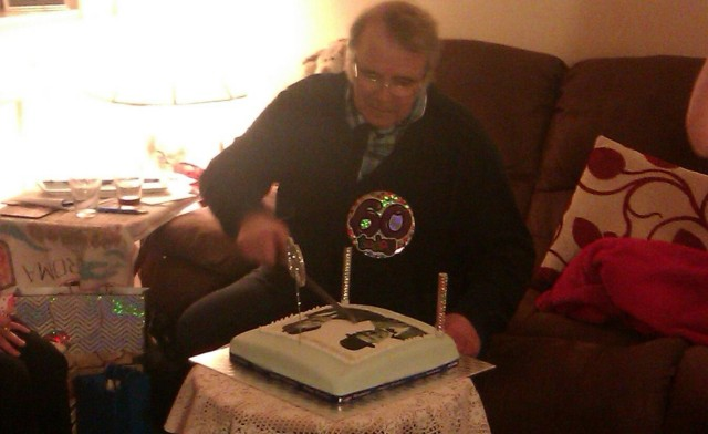 Paul cutting his cake.